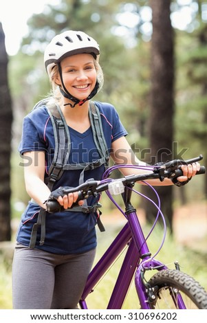 Young pretty happy biker looking at camera in the nature - stock photo