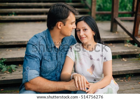 Young pretty happy couple sitting on wooden stairs in the park. Man and woman dating and flirting outdoors.
