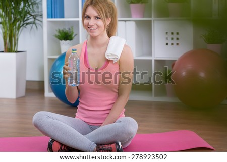Young pretty happy woman sitting on mat after training