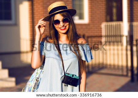 Young pretty hipster cheerful girl posing on the street at sunny day, having fun alone, stylish vintage clothes hat and sunglasses, travel concept , young photographer with vintage camera. - stock photo