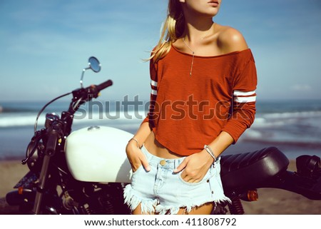 young pretty hipster girl Biker girl sitting  on vintage custom motorcycle Biker girl sitting Outdoor lifestyle portrait. jeans short denim, fashion style - stock photo