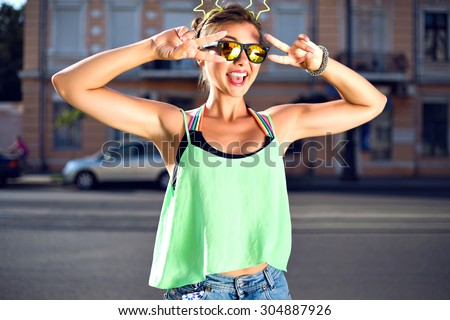 Young pretty hipster girl making funny grimaces and big amazing smile,wearing bright summer clothes, mirrored sunglasses and funny hair accessory with neon stars. fit sportive model, joy, travel. - stock photo