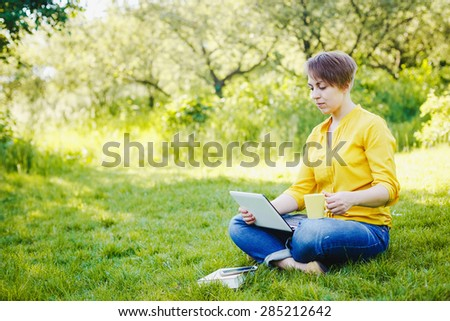 Young pretty hipster girl with laptop in a park - stock photo
