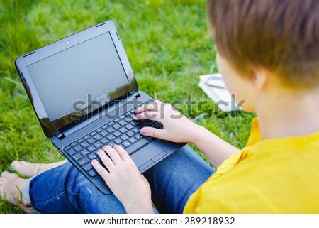 Young pretty hipster girl with laptop in a park