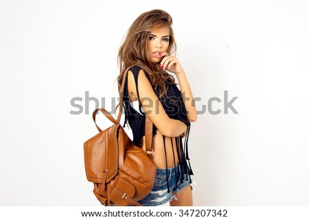 Young pretty hipster woman in black trendy t-short and bikini sitting on the floor against white wall.Have perfect long wavy hairstyle wearing sunglasses.Sensual woman wear cool outfit,denim outfit - stock photo