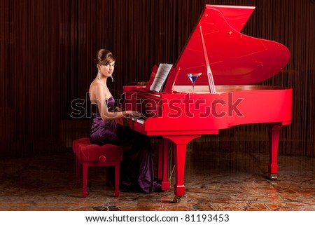young pretty lady, playing  the piano, posing at camera - stock photo