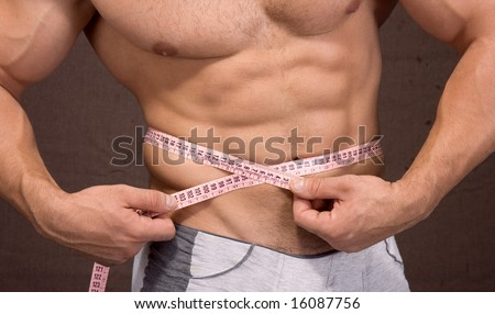 Young pretty man measuring his perfect body isolated on braun - stock photo