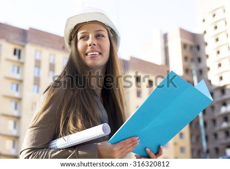 young pretty manager in hardhat at construction outside close up smiling - stock photo
