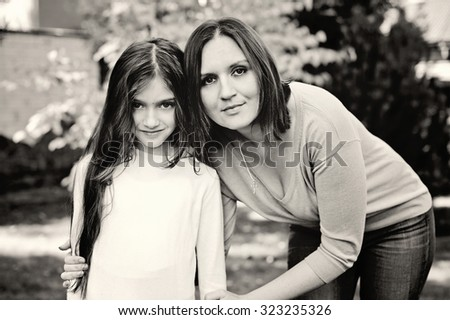 Young pretty mother and preteen age daughter outside at the beautiful sunny day black and white edition - stock photo