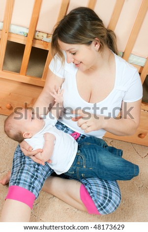 young pretty mother with a little baby sitting on the floor in living room and playing