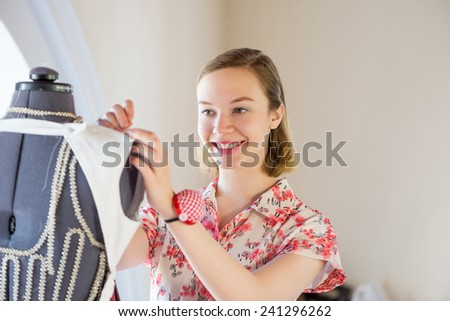 Young pretty needlewoman fitting dress on dummy