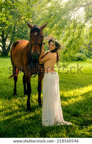 Young pretty nude brunette woman with horse in summer forest