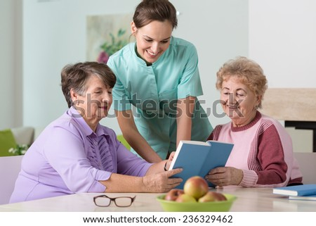 Young pretty nurse and two happy older women - stock photo