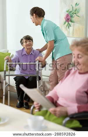 Young pretty nurse helping older patient to stand up - stock photo