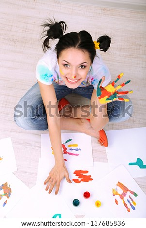 Young pretty painter with hands in paint, on gray background - stock photo