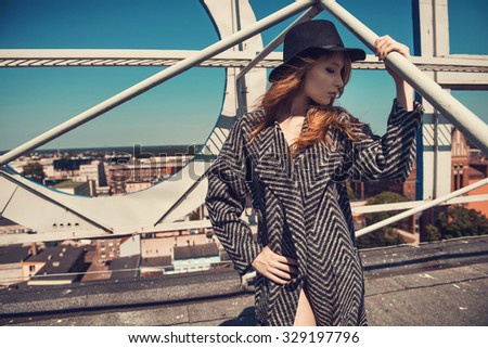 Young pretty red haired woman wearing coat, boots and black hat at the rooftop. Fashion photo - stock photo