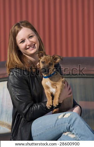 Young pretty red headed woman holding a puppy