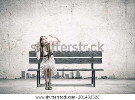 Young pretty scared asian woman sitting on bench - stock photo
