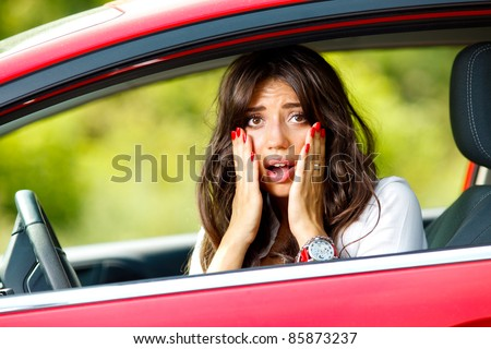 Young pretty scared woman in the car - stock photo