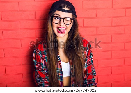 Young pretty seductive hipster woman having fun and showing long tongue and winked, wearing plaid shirt and clear glasses, long hairs and bright make up. Red urban wall background.