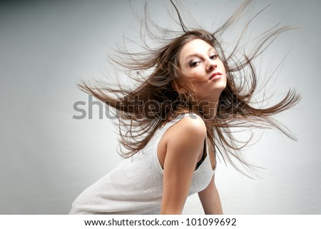 Young pretty sensual woman with flying hair on gray gradient background - stock photo