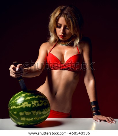 Young pretty sexy woman hold big knife in hands and trying to cut fresh red watermelon in underwear on a dark background