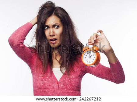 Young pretty shocked woman holding clocks in hands - stock photo