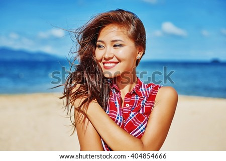 Young pretty smiling brunette girl portrait posing and having fun in summertime on the beach