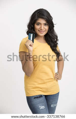 Young pretty smiling Indian girl showing her credit card to the camera. - stock photo