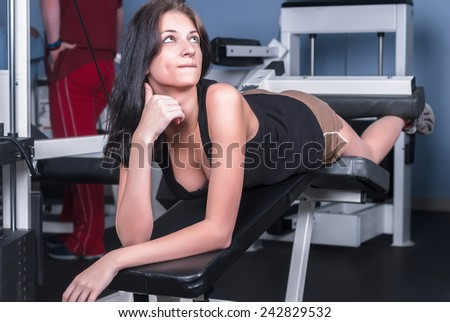 Young pretty sport woman trains in fitness center - stock photo
