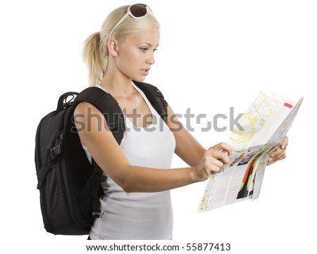 young pretty student girl in vacation looking for place on a map with rucksack - stock photo