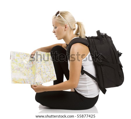 young pretty student girl in vacation sitting down and looking for place on a map