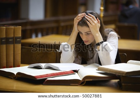 Young pretty student sitting at desk in old university library with books being overloaded with work and worried.