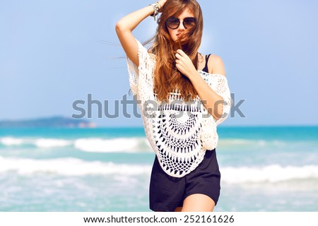 Young pretty stylish sensual woman posing at amazing tropical beach with blue ocean, enjoy her vacation and windy summer sunny day. Wearing playsuit and sunglasses. - stock photo