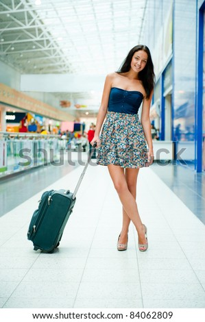 Young pretty stylish woman with luggage at the international airport. Waiting her flight at tax free shopping zone. - stock photo
