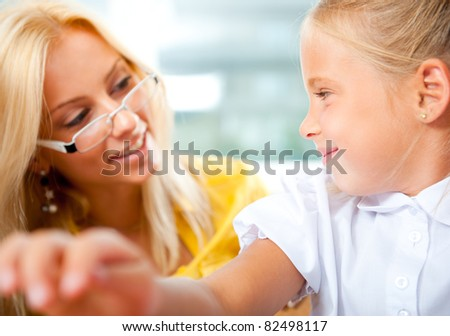 Young pretty teacher helping to her students to make exercise indoors at classroom. Horizontal Shot - stock photo