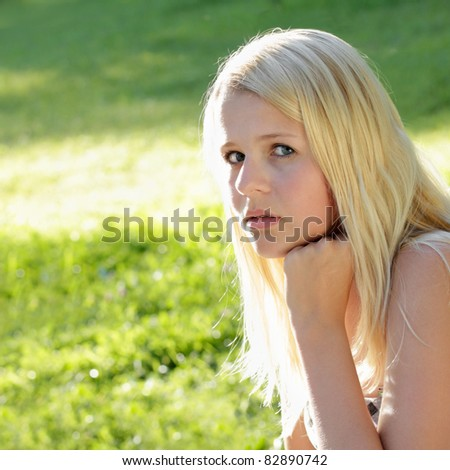 Young, pretty teenage girl, looking pensive. Sunny outdoor shot. - stock photo