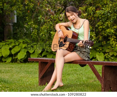 Young pretty teenager girl sitting in the park and playing guitar, singing - stock photo
