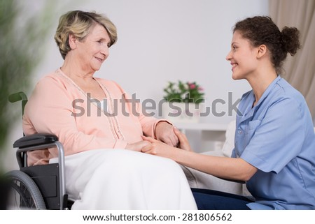 Young pretty thoughtful nurse and older lady on wheelchair - stock photo