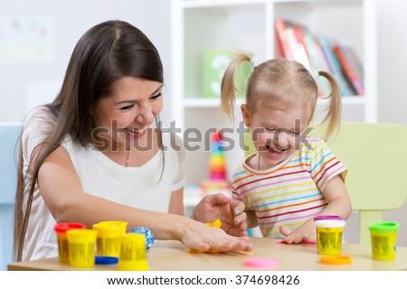 Young pretty woman and child girl playing with colorful clay in nursery - stock photo