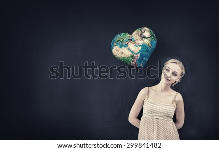 Young pretty woman and heart shaped Earth planet. Elements of this image are furnished by NASA - stock photo