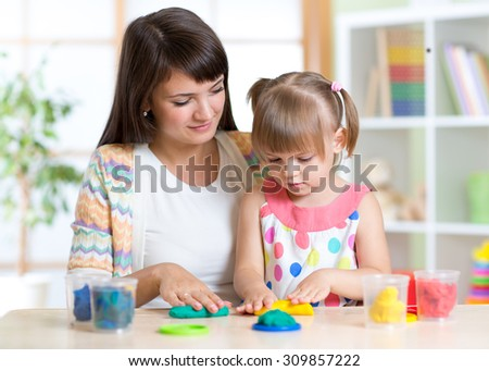 Young pretty woman and kid playing with colorful clay molding different shapes