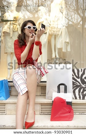 Young pretty woman applying lipstick while sitting in shop with shopping bags. - stock photo