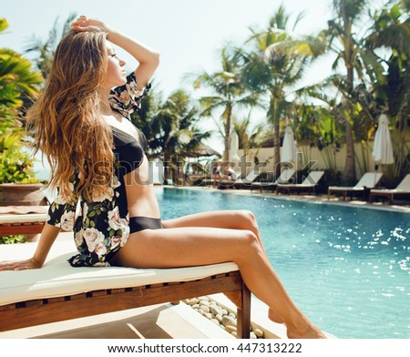 young pretty woman at swimming pool relaxing in chair, fashion l - stock photo