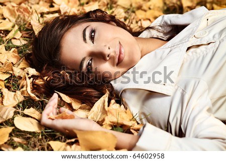 Young pretty woman at the autumn park - stock photo