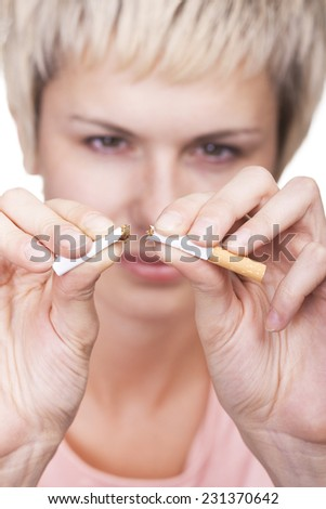 Young pretty woman breaking cigarette over white background  - stock photo