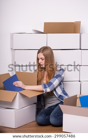 Young pretty woman carefully packing book to boxes