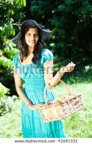 young pretty woman carrying a basket of litchis in orchard