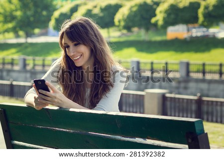 Young pretty woman chatting using phone. Smiling caucasian girl have fun with using smartphone in park - stock photo