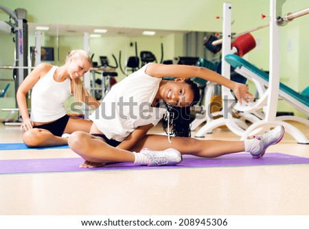 Young pretty woman doing exercises at the fitness club - stock photo